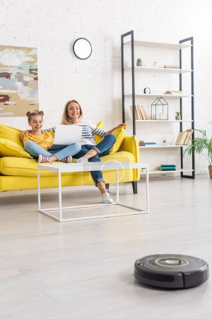 Photo for Mother smiling, hugging daughter with laptop on sofa near coffee table and looking at robotic vacuum cleaner on floor in living room - Royalty Free Image