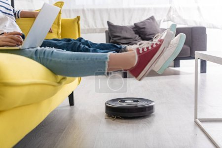 Cropped view of kid with laptop near mother with raised legs on sofa and robotic vacuum cleaner on floor in living room