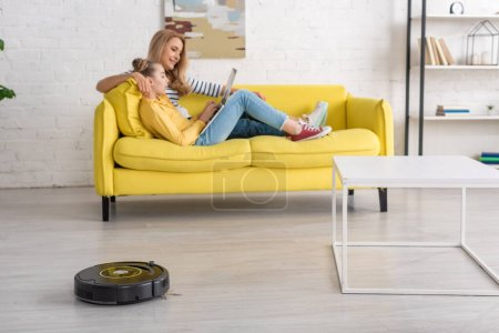 Mother and daughter with laptop resting on sofa near coffee table and robotic vacuum cleaner on floor in living room