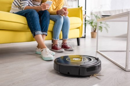 Photo for Cropped view of woman with smartphone and daughter on sofa near coffee table and robotic vacuum cleaner on floor in living room - Royalty Free Image
