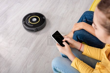 Cropped view of child with smartphone and mother near robotic vacuum cleaner on floor in living room