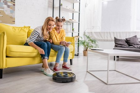 Photo for Happy woman and kid with smartphone smiling and looking at robotic vacuum cleaner near coffee table on floor in living room - Royalty Free Image