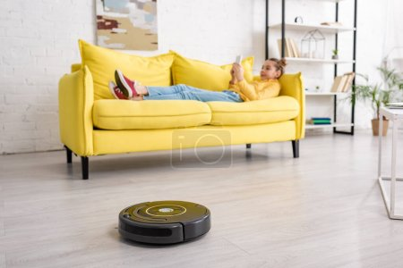 Photo for Selective focus of kid with smartphone lying on sofa near robotic vacuum cleaner on floor in living room - Royalty Free Image