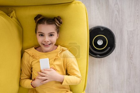 Photo for Top view of cute child with smartphone smiling, looking at camera and lying on sofa near robotic vacuum cleaner on floor in living room - Royalty Free Image