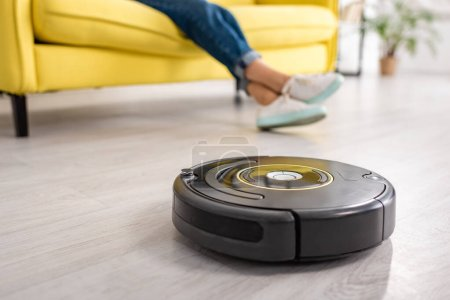 Photo for Cropped view of female legs with robotic vacuum cleaner on floor in living room - Royalty Free Image