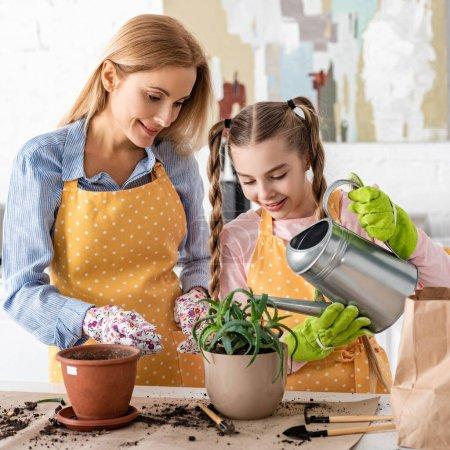 Photo pour Mère et fille mignonne arrosage aloès en pot de fleurs près des outils de jardinage sur la table dans la cuisine - image libre de droit