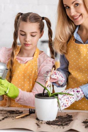 Photo pour Femme avec pelle et pot de fleurs avec aloès souriant et jolie fille tenant pot d'arrosage près de la table dans la cuisine - image libre de droit