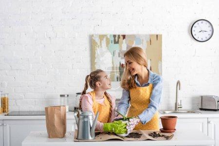 Photo pour Mère et fille mignonne se regardant et touchant pot de fleurs avec aloès près du pot d'arrosage et sac en papier sur la table avec le sol - image libre de droit