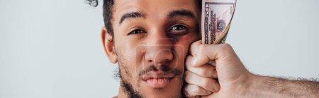 Foto de La mano masculina que tiene billetes en dólares cerca de la cara del hombre africoamericano con la bruma aislada en gris, disparo panorámico. - Imagen libre de derechos