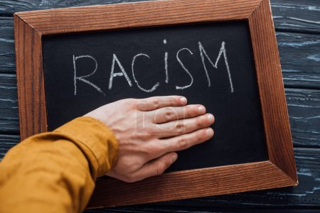 Photo for Cropped view of man holding hand near blackboard with racism lettering on dark wooden background - Royalty Free Image