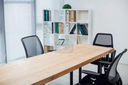 Photo pour Table et chaises en bois près du rack avec des dossiers en papier dans le bureau - image libre de droit