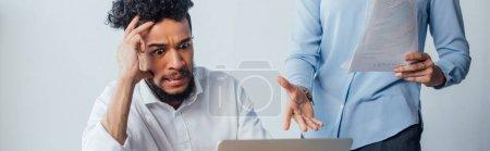Foto de Foto panorámica de espeluznantes afriamericanos mirando al ordenador portátil cerca de empresarias que tienen documentos. - Imagen libre de derechos