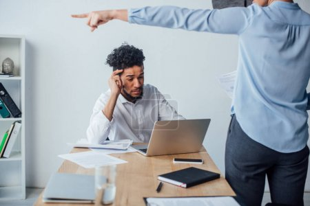 Photo pour Concentration sélective de l'homme afro-américain en utilisant un ordinateur portable près d'une femme d'affaires pointant du doigt au bureau - image libre de droit