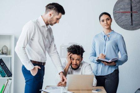 Photo pour Des gens d'affaires multiethniques se tenant près d'un homme d'affaires américain africain confus à la table du bureau - image libre de droit