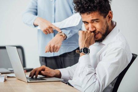Photo pour Focus sélectif d'un homme d'affaires africain américain regardant la caméra pendant qu'il travaille sur un ordinateur portable près d'un collègue pointant sur une montre-bracelet - image libre de droit