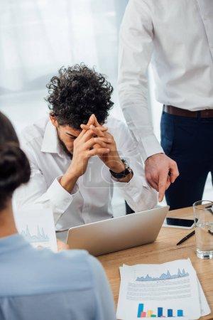 Photo pour Concentration sélective de l'homme d'affaires pointant vers l'ordinateur portable à triste collègue afro-américain au bureau - image libre de droit
