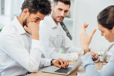Selective focus of african american businessman using laptop near multiethnic colleagues in office