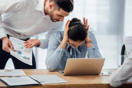 Photo pour Concentration sélective de l'homme d'affaires pointant vers les papiers près de collègue mexicain oreilles vacillantes dans le bureau - image libre de droit