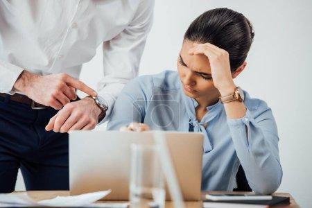 Photo pour Concentration sélective de l'homme d'affaires pointant vers montre-bracelet près triste collègue mexicain en utilisant un ordinateur portable dans le bureau - image libre de droit