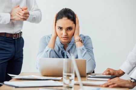 Photo pour Concentration sélective de la femme d'affaires mexicaine couvrant les oreilles près de collègues multiethniques au bureau - image libre de droit