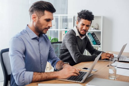 Selective focus of confused african american businessman looking at colleague using laptop in office