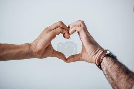 Photo pour Vue recadrée des hommes montrant un signe d'amour avec les mains isolées sur gris - image libre de droit