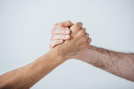 Photo pour Vue recadrée des hommes tenant les mains isolées sur gris - image libre de droit
