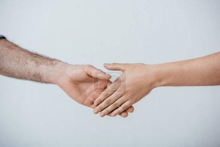 Photo pour Vue recadrée de l'homme et de la femme serrant la main isolés sur gris - image libre de droit