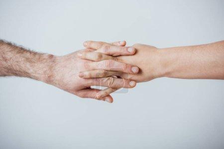Photo pour Vue recadrée de l'homme et de la femme tenant les mains isolées sur gris - image libre de droit