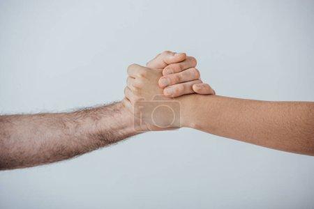 Photo pour Vue recadrée de deux hommes tenant les mains isolées sur du gris - image libre de droit