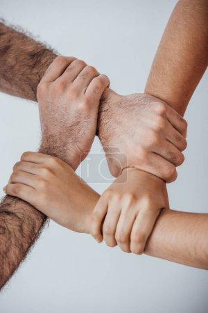 Photo pour Vue recadrée d'hommes faisant un geste d'unité avec les mains isolées sur le gris - image libre de droit