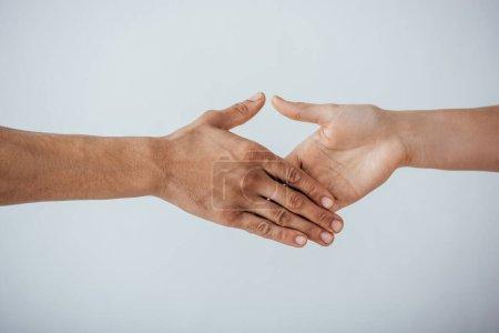 Photo pour Vue recadrée d'hommes tenant la main pour une poignée de main isolée sur gris - image libre de droit