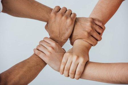 Photo pour Vue recadrée d'hommes multiethniques faisant un geste d'unité isolés sur le gris - image libre de droit