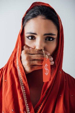 Photo pour Homme main tenant étiquette de prix avec signe dollar et couvrant la bouche à pleurer femme indienne en sari isolé sur gris - image libre de droit