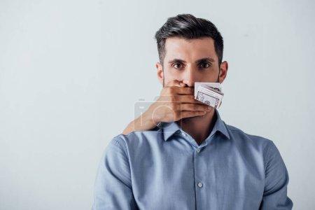 Photo pour Billets libellés en dollars détenus à la main par un homme et couvrant la bouche de l'homme isolé sur gris - image libre de droit