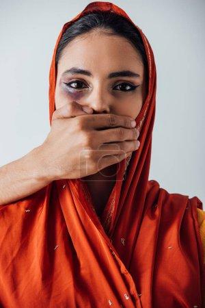 Photo pour Main masculine couvrant la bouche à la femme indienne avec ecchymose isolée sur gris - image libre de droit
