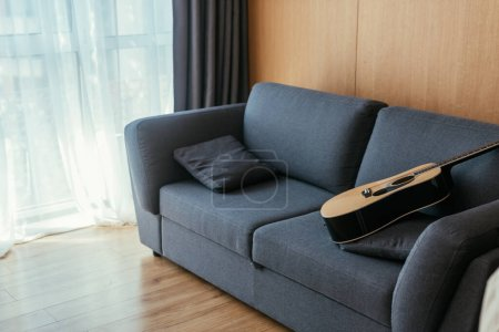 Photo for Interior of living room with acoustic guitar on grey sofa and sunlight in large window - Royalty Free Image