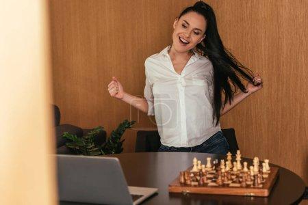 Photo pour Foyer sélectif de femme excitée montrant geste gagnant près de l'échiquier et ordinateur portable sur la table - image libre de droit