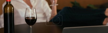 Photo for Selective focus of glass and bottle of red wine near woman, cropped view, horizontal image - Royalty Free Image