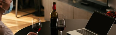 Photo for Cropped view of young woman in medical mask near laptop with blank screen, glasses ad bottle of red wine, panoramic shot - Royalty Free Image