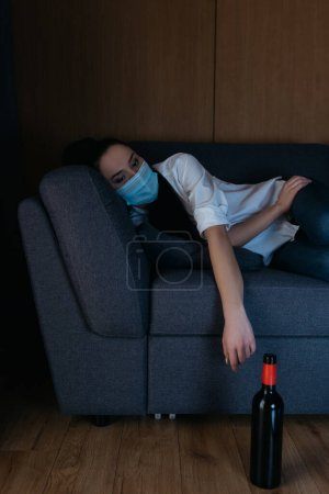 Photo for Depressed woman in medical mask lying on sofa near bottle of wine on floor - Royalty Free Image