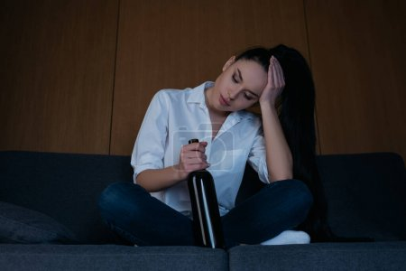 Photo for Depressed woman touching head while sitting on sofa with bottle of wine - Royalty Free Image