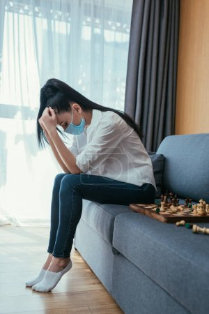Photo for Depressed woman in protective mask sitting on sofa near chessboard with bowed head - Royalty Free Image