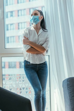 Photo for Depressed girl in medical mask standing with crossed arms near window at home - Royalty Free Image