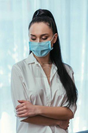 Photo pour Fille déprimée dans le masque médical debout avec les bras croisés à la maison - image libre de droit