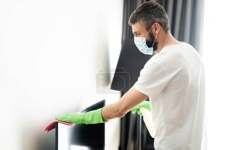 Photo pour Vue latérale de l'homme dans le masque médical nettoyage tv avec chiffon et détergent dans le salon - image libre de droit
