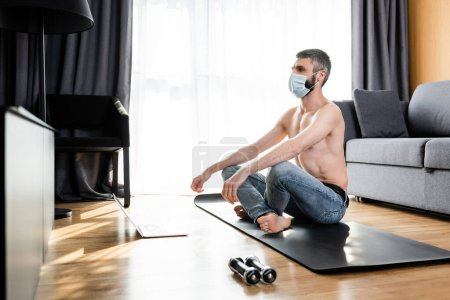 Photo for Side view of shirtless man in medical mask sitting on fitness mat near dumbbells and laptop at home - Royalty Free Image