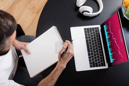 Photo pour Vue aérienne du télétravailleur tenant un ordinateur portable et un stylo près d'un ordinateur portable avec des graphiques à l'écran - image libre de droit