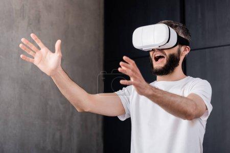 Photo pour Homme choqué utilisant casque de réalité virtuelle à la maison - image libre de droit