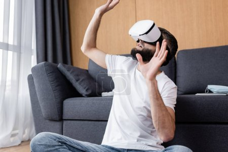 Photo for Man in vr headset playing video game on floor in living room - Royalty Free Image